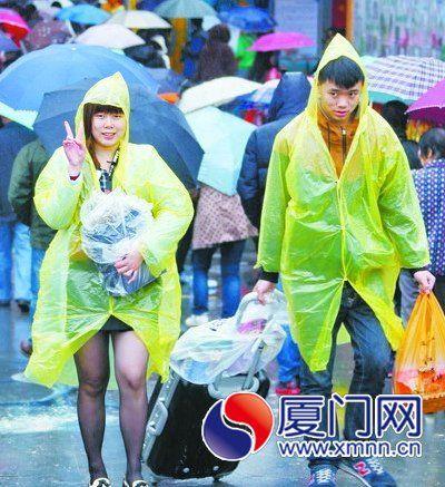 游客冒雨在曾厝垵游玩。(本报记者 王协云 摄)