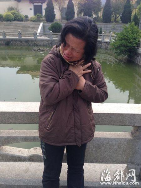 死者母亲把儿子的照片搂在胸口,在放生池旁痛哭