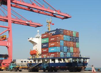 10月13日,一艘货轮在江苏连云港港口码头卸载集装箱。 新华社发(耿玉和/摄)