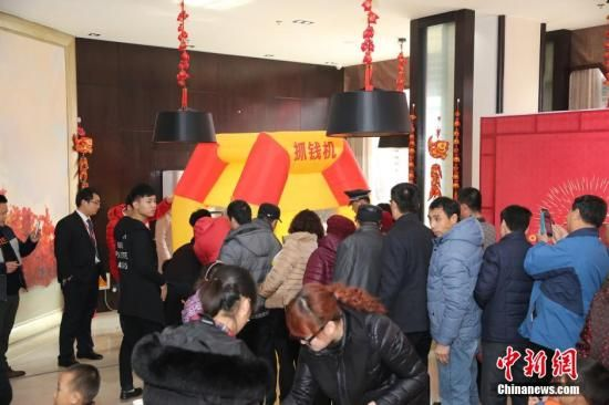 """资料图:2016年2月27日,山东东营,看房的市民在商家设置的""""抢钱机""""内抢着飞舞的人民币,抢到的人民币归市民所有。图片来源:视觉中国"""