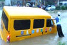 女交警暴雨积水中撑起幼儿校车