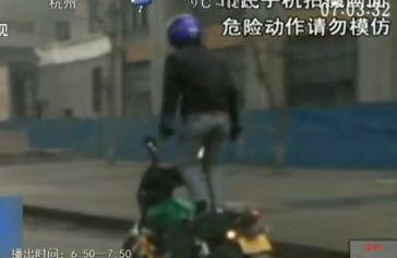实拍男子车流中行驶摩托车上站立耍杂技